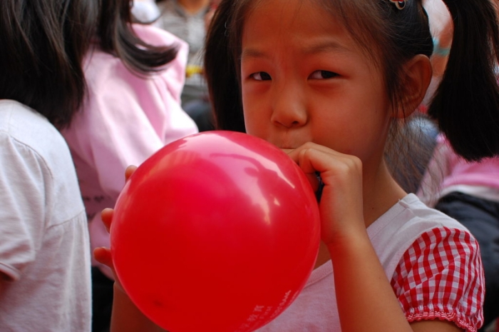 1024px-Girl_inflating_a_red_balloon